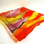 Kunst in gekleurd glas, schaal van Rubaniuk in mooie kleuren die op het oppervlak eronder reflecteren ...