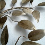 Het metalen wandsculptuur heeft een patine met daardoor een antiek zilverachtige uitstraling, met satijnglans