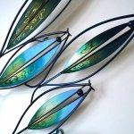 Moderne kunst in metaal met mooie bewerkingen in prachtige kleuren, die in warm (zon-)licht intenser worden